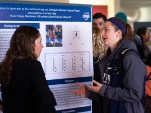 Two female students talking in front of a poster that details a student research project.