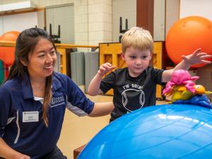 A female student works with a small male child, who is standing near an an exercise ball.