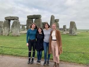 Four female students pose in front of the standing stones of Stonehenge.