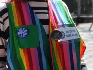 Focused shot of a person's chest. The person is wearing a rainbow striped vest adorned with pro-choice pins.