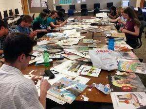 Students cutting magazines for a project in a classroom.
