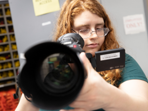 Student holds camera while adjusting the lens.