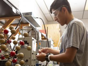student works with scientific equipment in a lab