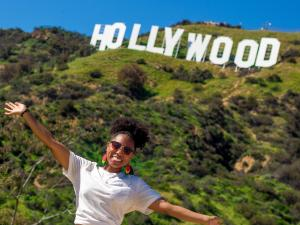 Young woman posing with arms held wide beneath the Hollywood sign.