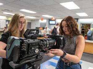 Two young women inspect a film camera prior to operation.
