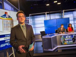 Student sportscaster speaking on set with news anchors seated in the background.