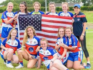 A group of women in athletic uniforms pose with the U.S. flag