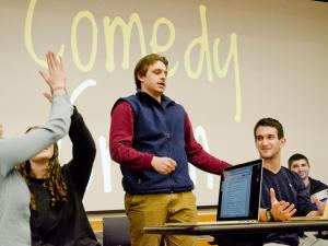 "Students around open laptops discuss the topic of ""comedy,"" written in large letters on a board behind them."