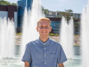 A student in front of a fountain.