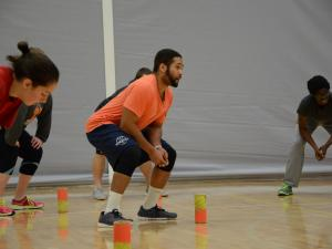 A student in a bright orange shirt is crouched down in a gym practicing for a physical education class.