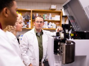 professor works with students in the lab