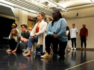Young people kneeling in a rehearsal space