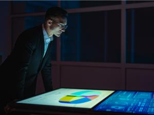 A man in a suit looks at graphs on a screen