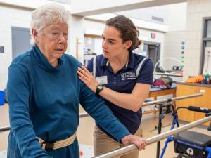 A student in a blue shirt is working with an elderly patient helping them with standing up.