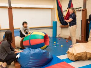 A group of faculty and students are in the occupational therapy clinic with play mats working with a child who is playing