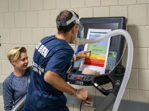 A person in a blue shirt is running on a treadmill with a mask attached to his face while a student stands nearby measuring his breath. The person is pointing to a posterboard that indicates how much exertion they are feeling while running.