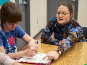 A student wearing glasses and a long sleeve colorful shirt  is sitting at a table with a young client in a blue shirt pointing at a piece of paper on the table. The boy is writing on the piece of paper with a marker.