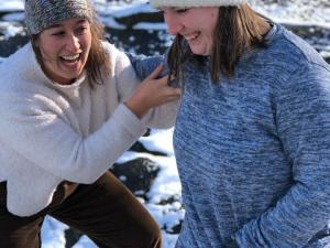 A group of two students are playing in the snow.