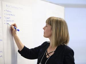 woman writing on a large sheet of paper
