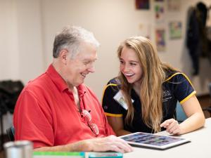 student helping older person
