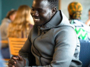 a student of color smiling, sitting down in a gray nike hoodie enjoying a conversation.