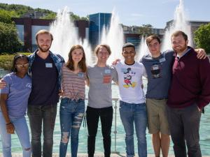 A group of students posing in front of fountains.