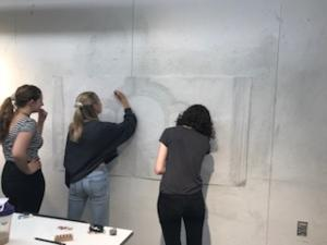three students drawing on a wall mural