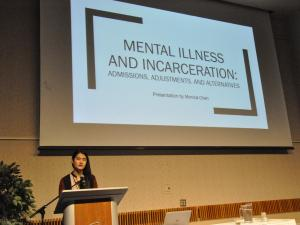 a student standing a podium to present on mental health and mass incarceration