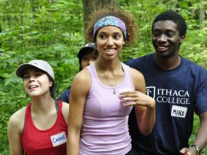 3 1st year MLK Scholars on a low ropes course smiling and welcoming the next challenge