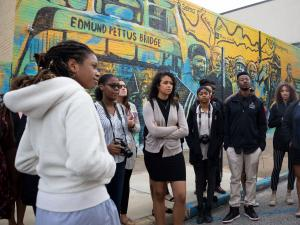 A group of MLK Scholars infront of a mural of civil rights activists in downtown Montgomery, AL