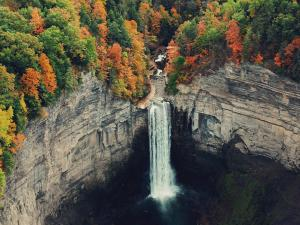 Tall waterfall amongst trees in autumn.