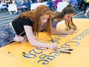 two women sign a banner that reads Ithaca College class of 2020