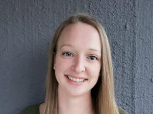 This is a photo of Courtney Yehl. Courtney is standing against a grey background. Courtney is wearing a long sleeve green shirt.