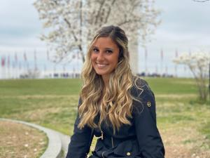 This is a photo of Danielle Pasquale. Danielle is seated outside, with green grass and a tree behind where Danielle is sitting. Danielle is wearing a black coat and pants.