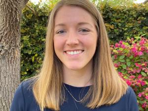 This is a photo of Hannah Thomas. Hannah is smiling at the camera with long blond hair. Hannah is wearing a long sleeve blue shirt. Hannah is standing outdoors, in front of a tree.
