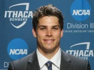 This is a photo of Jared Bauer. Jared is wearing a dark suit with a white shirt and blue striped tie. He is standing in front of a Ithaca Athletics background showing Division III athletics.