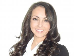This is a photo of Natalie Knight. Natalie is wearing a white ruffled shirt underneath a black blazer. Natalie has long dark curly hair.