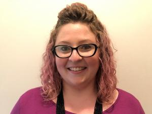 This is a photo of Sarah O'Hagen. Sarah is wearing a long sleeve purple shirt and a long black necklace around the neck. Sarah is wearing glasses.