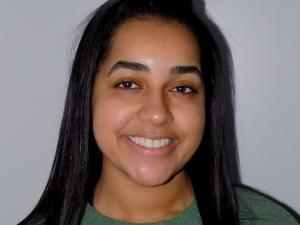 This is a photo of Taylor Larkin. Taylor is smiling at the camera with long black hair over the shoulders. Taylor is wearing a long sleeve green shirt.