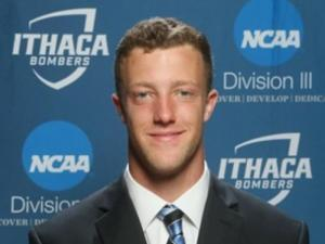 This is a photo of Tyler Winslow. Tyler is wearing a dark blue suit with a white shirt and blue striped tie. Tyler is standing in front of an Ithaca Athletics Division III background.