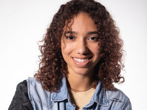 a young woman with curly brown hair smiling in a denim top
