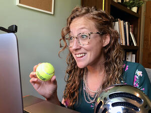 professor holding a tennis ball in front of a laptop
