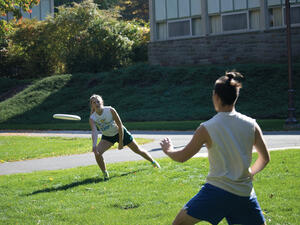 Two students playing frisbee outdoors.