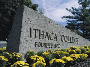 stone entrance to ithaca college with flowers on a sunny day