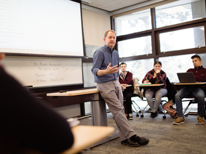 A male professor leavinging against a desk lecturing to a classroom full of students