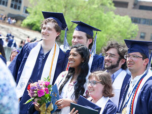 group of graduates in caps and gowns poses together