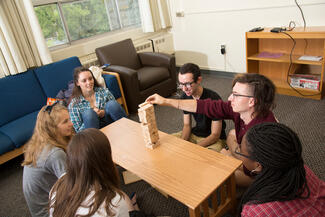 Students play a game in a residential building lounge