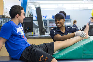 A physical therapy student examines the ankle of a student athelete