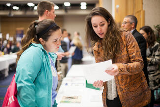 Students review information at a career fair on campus.