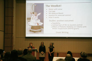 Three presenters in front of a screen showing a baby on a robot